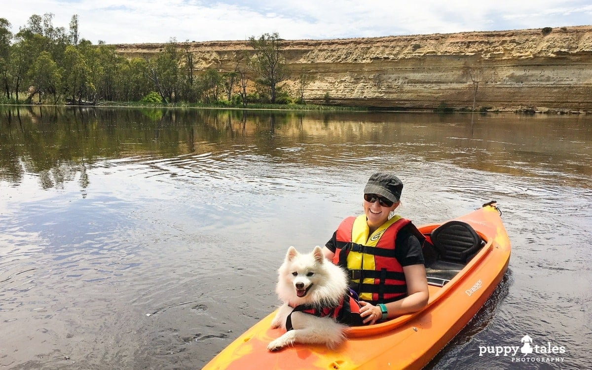 Kerry Martin and her dog Keiko canoeing whilst on a houseboat holiday along the Murray River in Victoria Australia