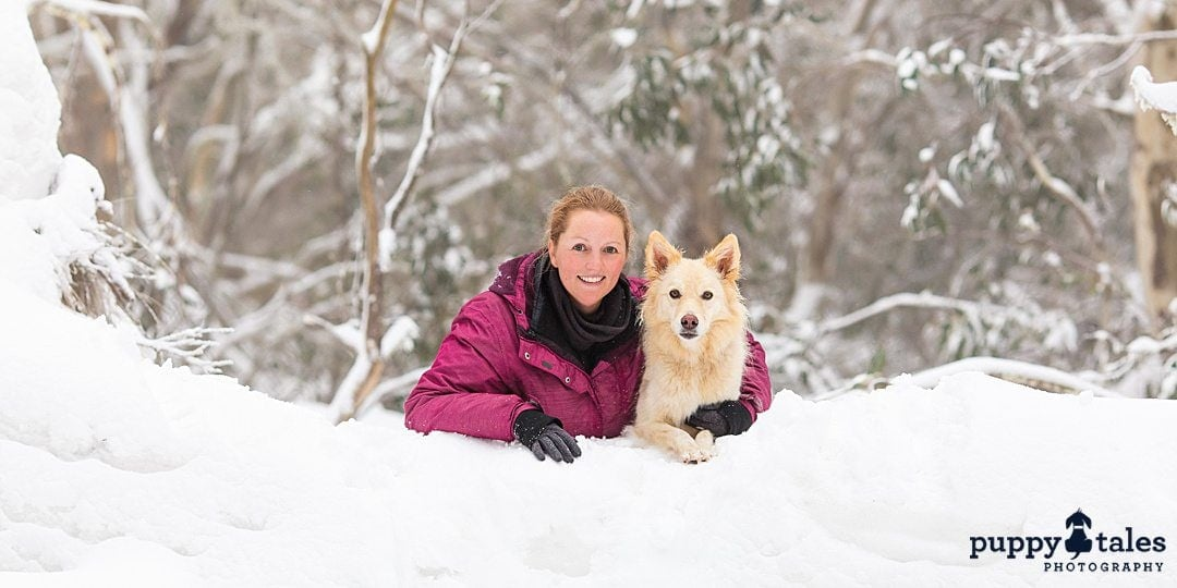 a woman wearing a winter jacket posing for the camera with her dog
