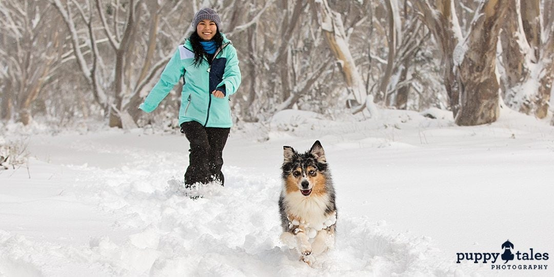 a woman enjoying the snow with her dog